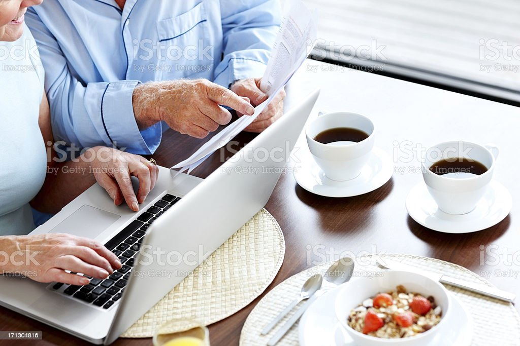 Cropped image of senior couple calculating their monthly expenses at...