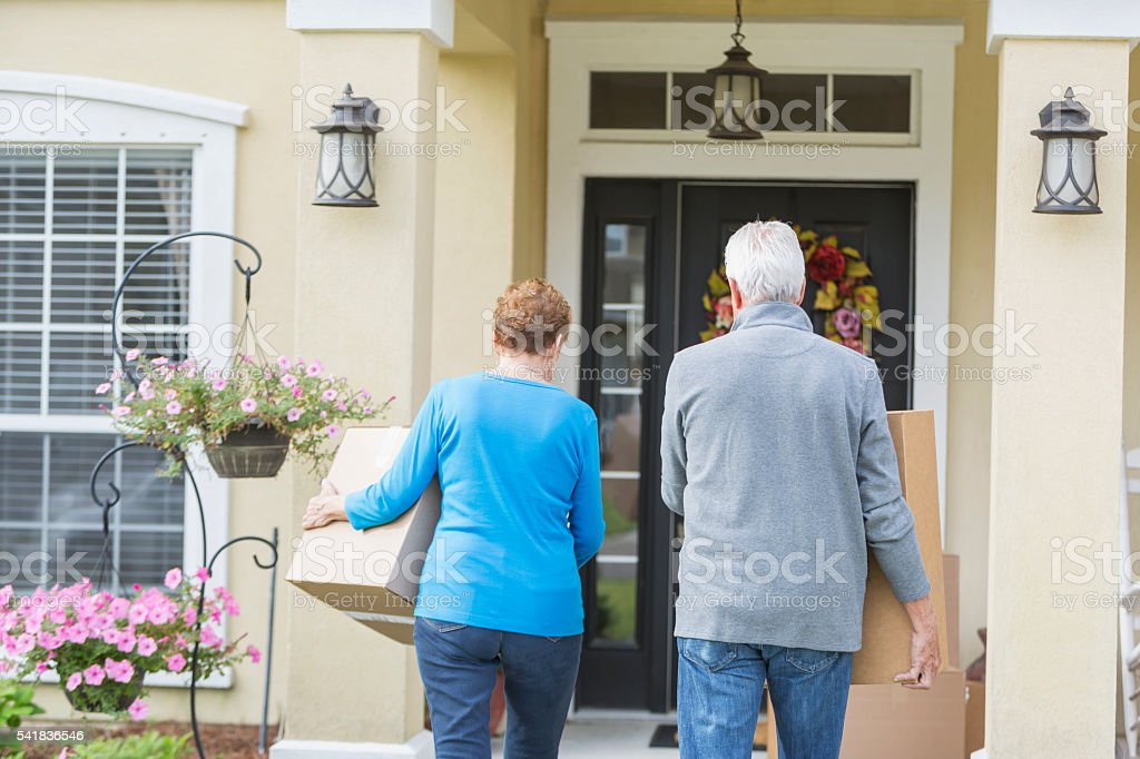 Senior couple carrying boxes to front door of house stock photo