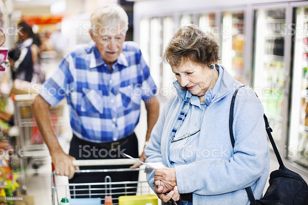 Senior couple check shopping list in supermarket aisle stock photo