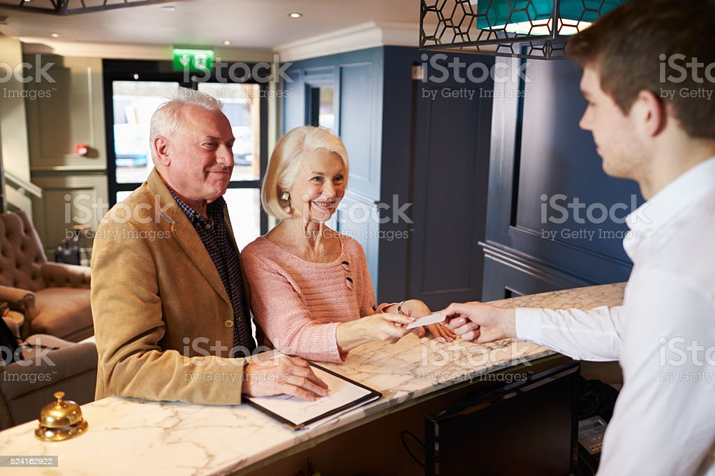 Senior Couple Checking In At Hotel Reception stock photo