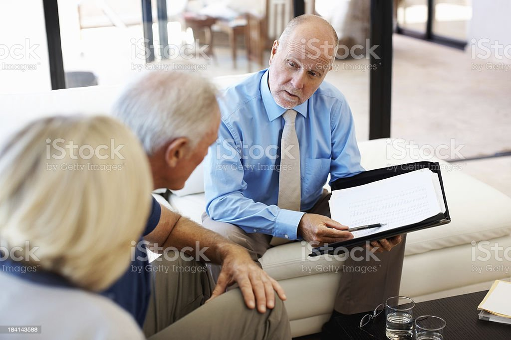 Senior couple consulting a financial planner at home royalty-free stock photo