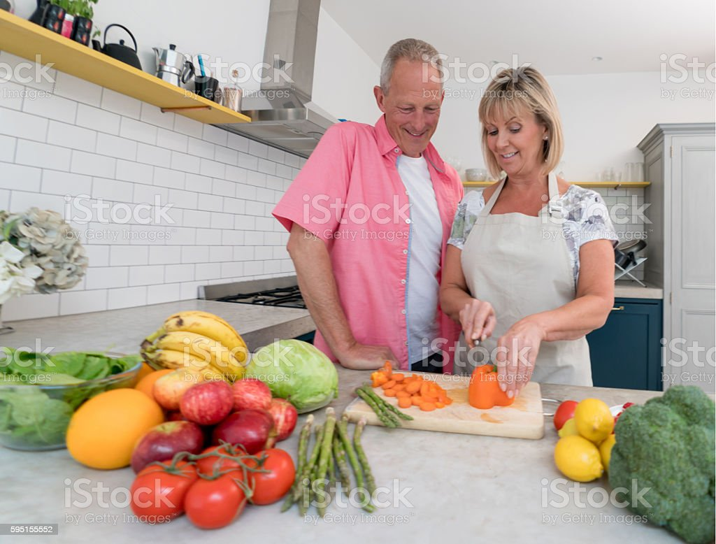 Senior couple cooking at home stock photo