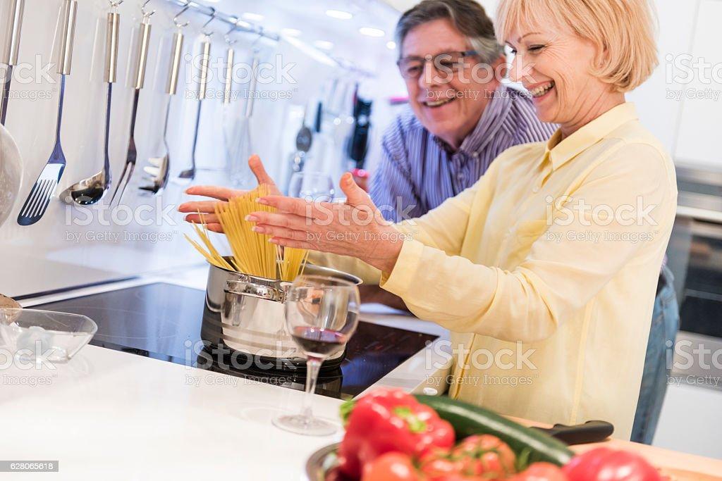 Senior couple cooking spaghetti stock photo