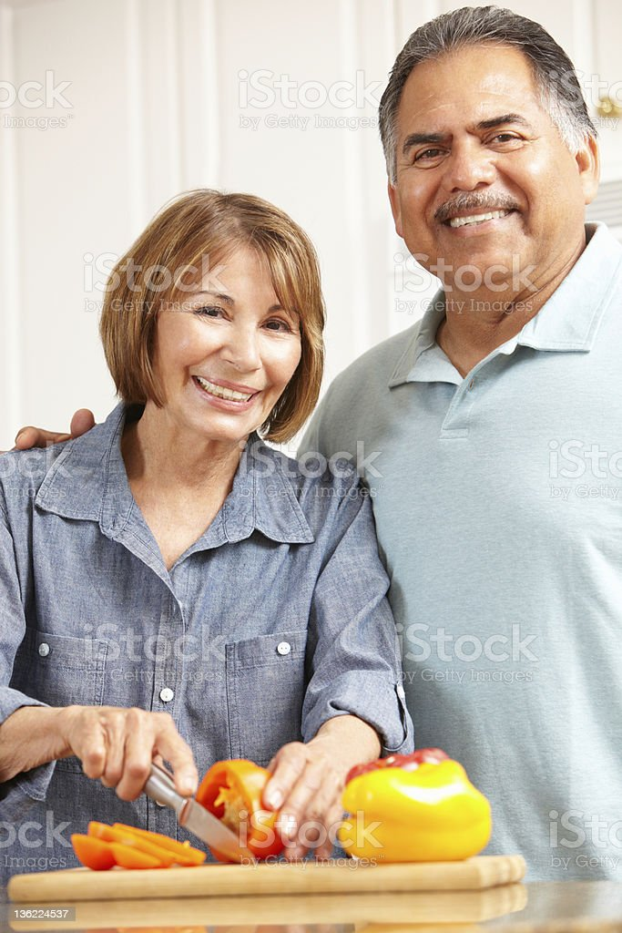 Senior couple cooking together in kitchen stock photo