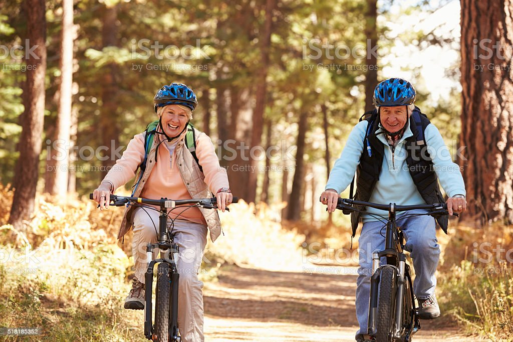 Senior couple cycling on forest trail, California stock photo