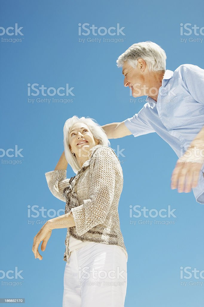 Senior couple dancing against blue sky royalty-free stock photo