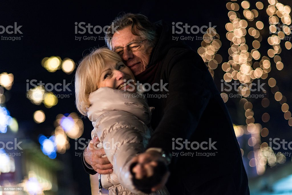 Senior couple dancing in the city at night stock photo