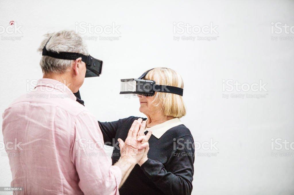 Senior couple dancing with virtual reality smartphone stock photo
