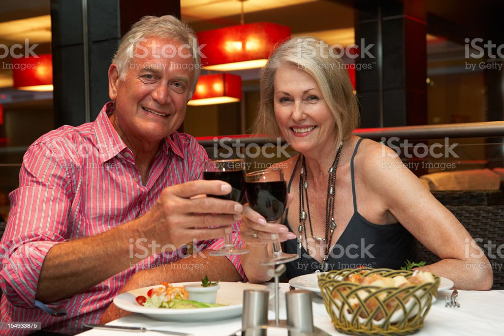 Senior couple dining at a fancy restaurant enjoying food royalty-free stock photo