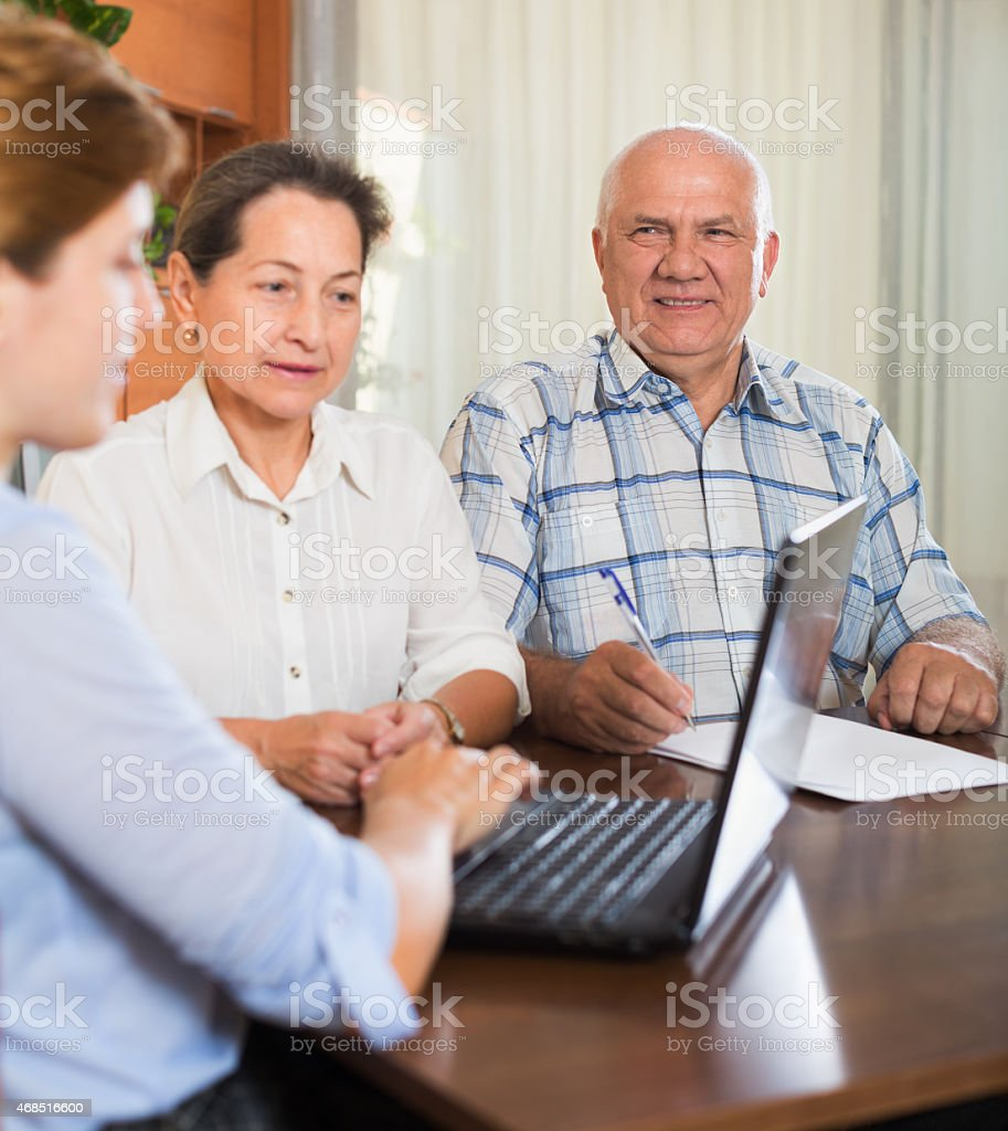 Senior couple discussing options with agent stock photo