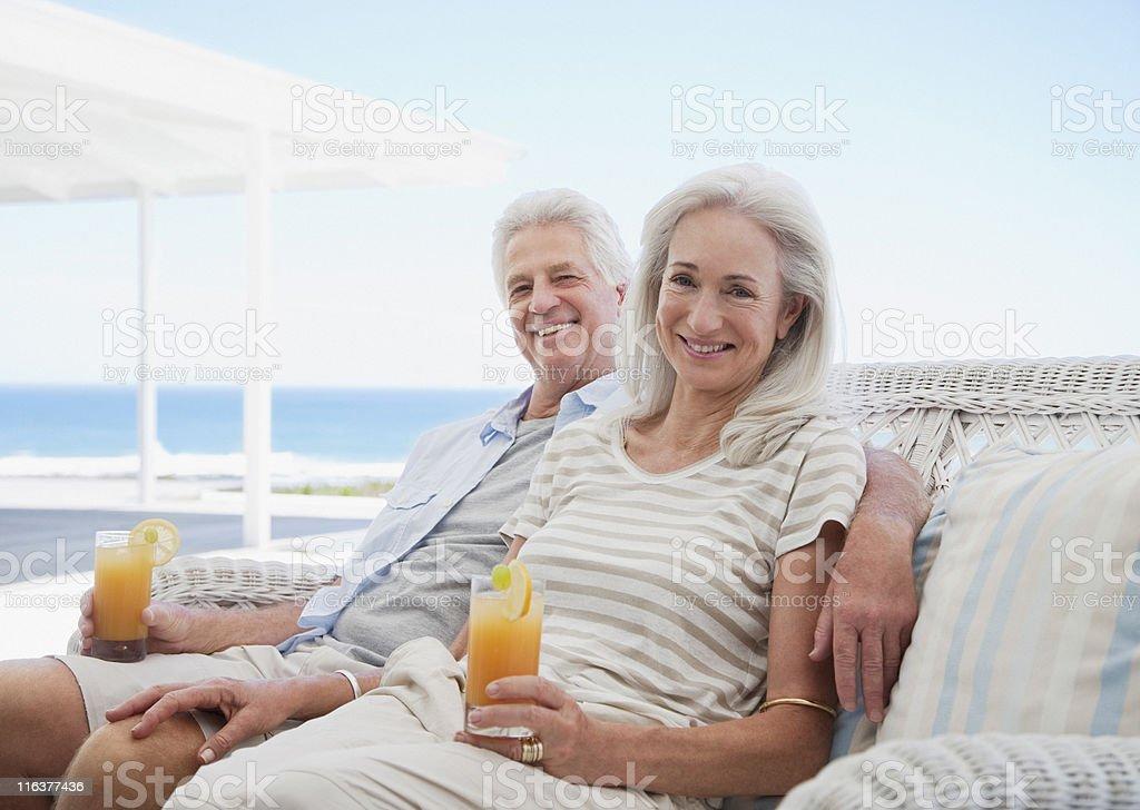 Senior couple drinking cocktails on beach patio stock photo