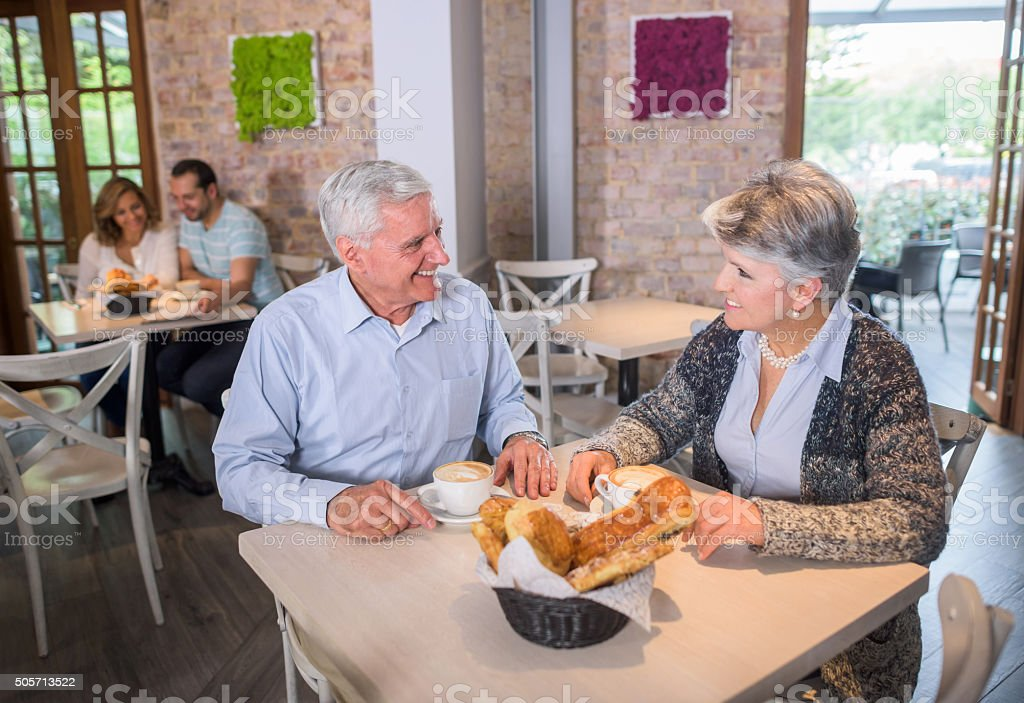 Senior couple drinking coffee at a cafe stock photo