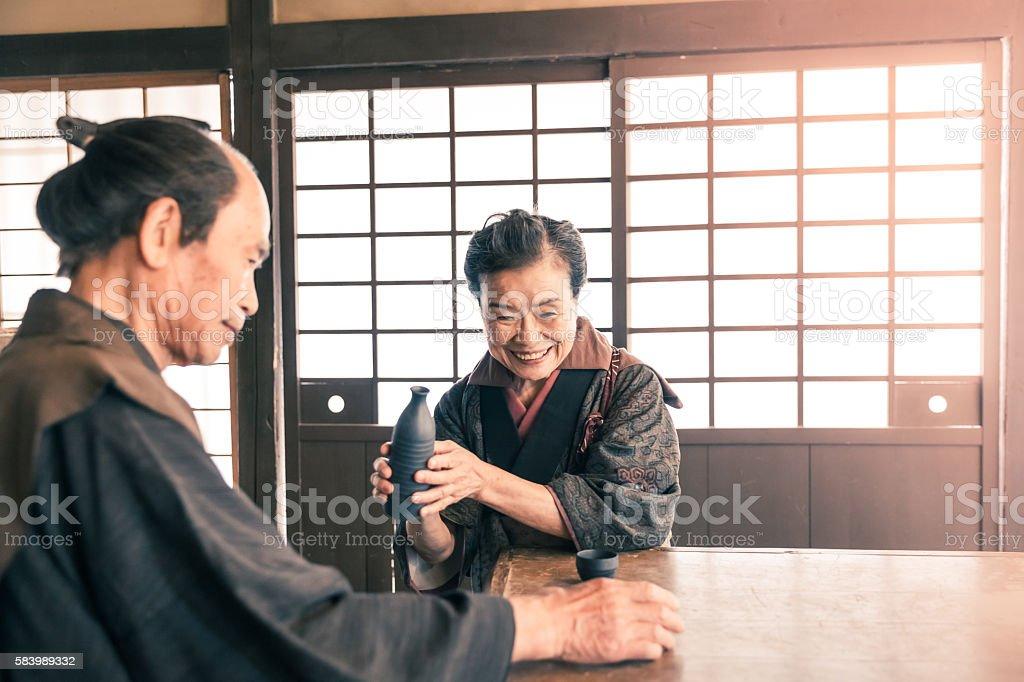 Senior couple drinking sake in front of shoji doors stock photo