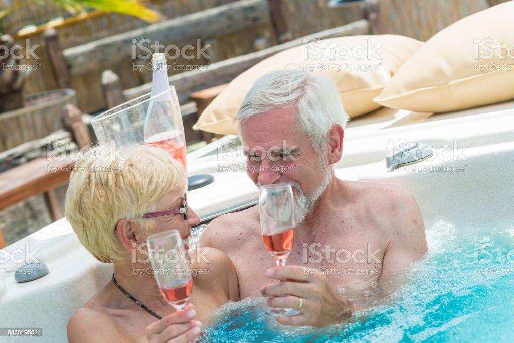 Senior Couple Drinking Wine in Jacuzzi stock photo