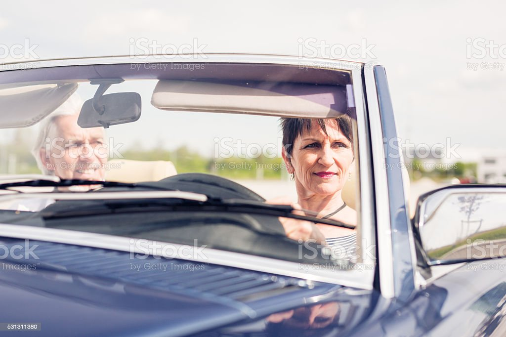 senior couple driving a convertible classic car stock photo
