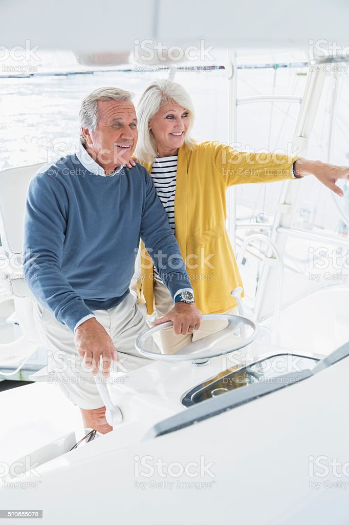 Senior couple driving boat, looking ahead, pointing stock photo
