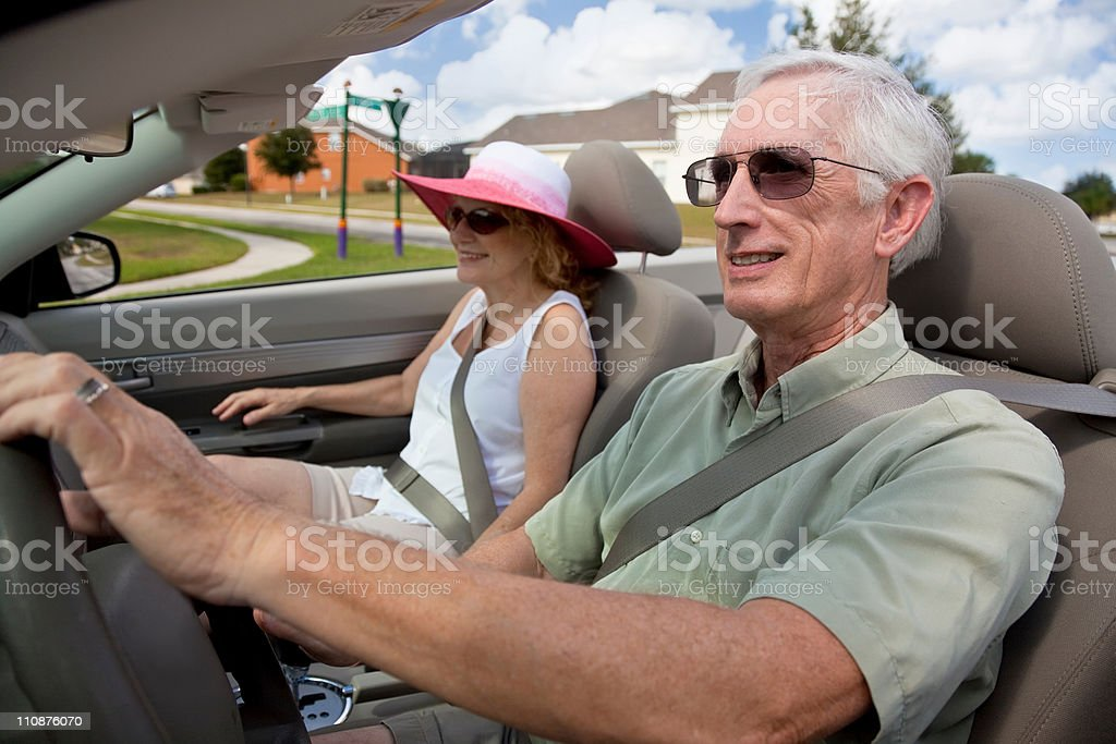 Senior Couple Driving Convertible Car Wearing Sunglasses stock photo