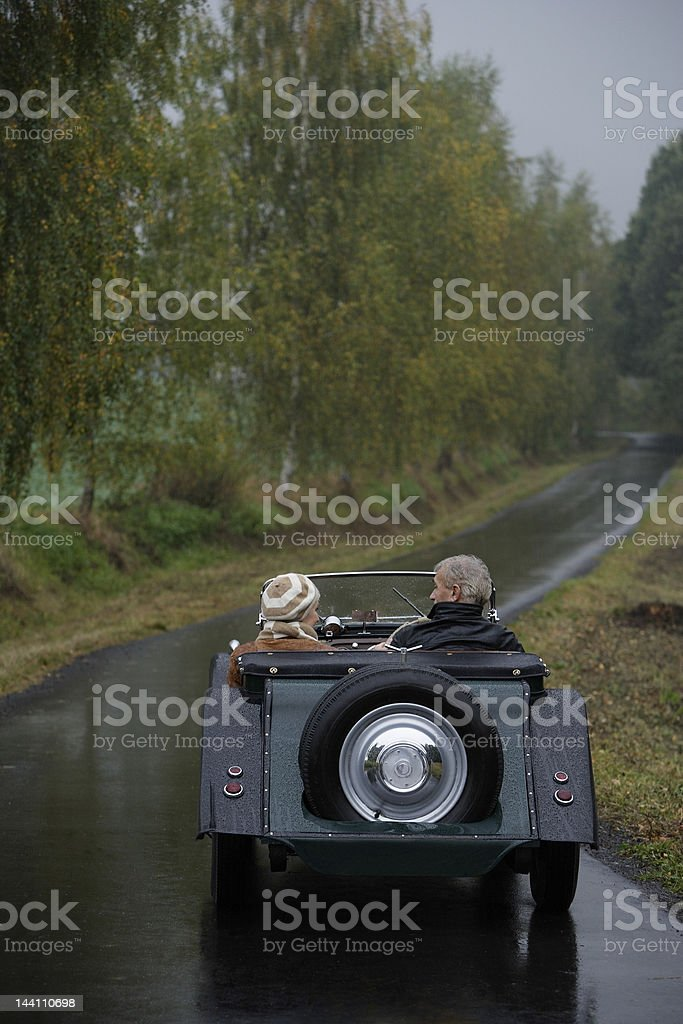 Senior couple driving down country road in antique car stock photo
