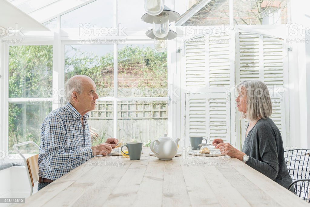 Senior couple eating breakfast in a conservatory stock photo