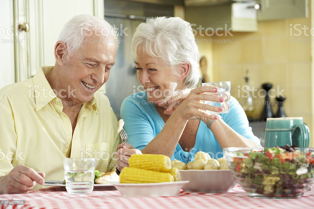 Senior Couple Eating Meal Together In Kitchen royalty-free stock photo