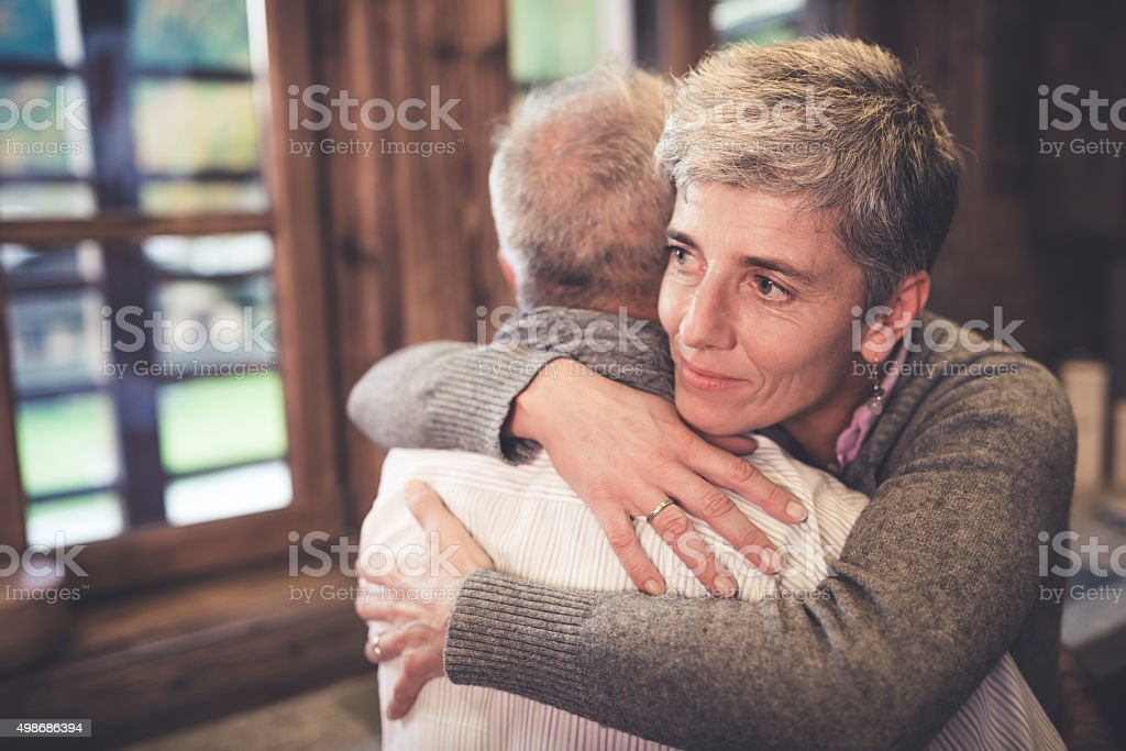 Senior couple embrace in kitchen stock photo