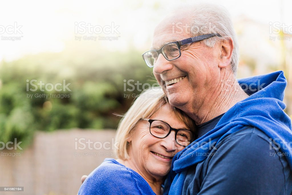 Senior couple embracing each other in backyard stock photo