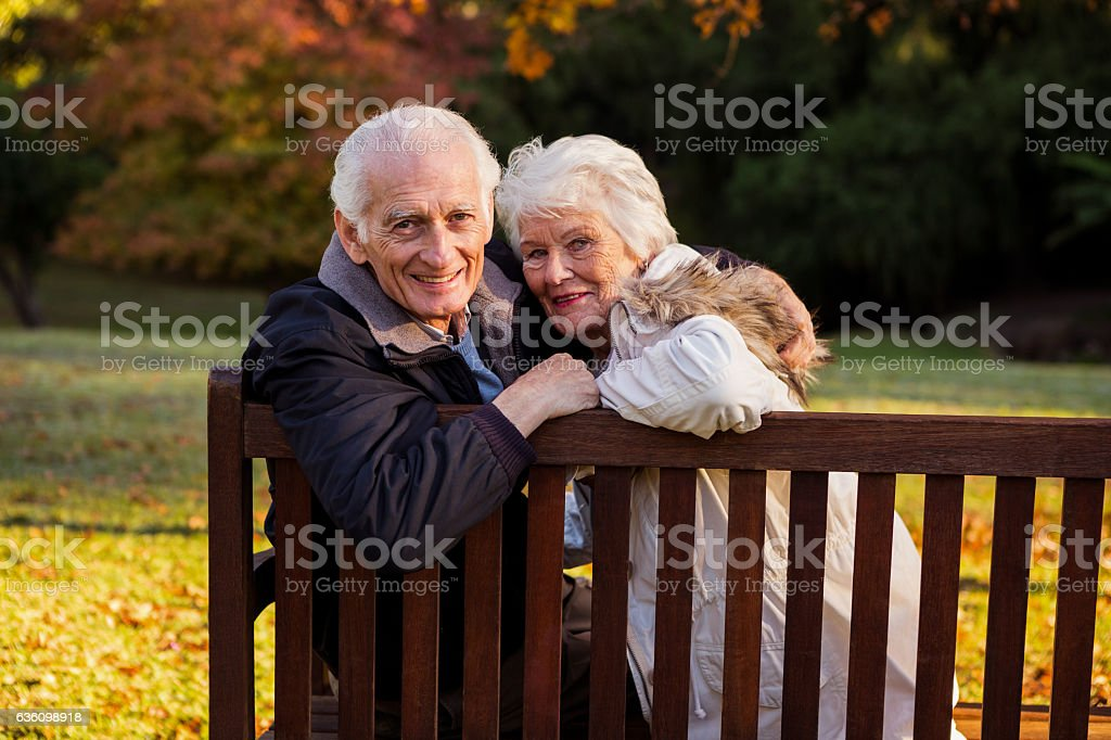 Senior couple embracing on a bench stock photo