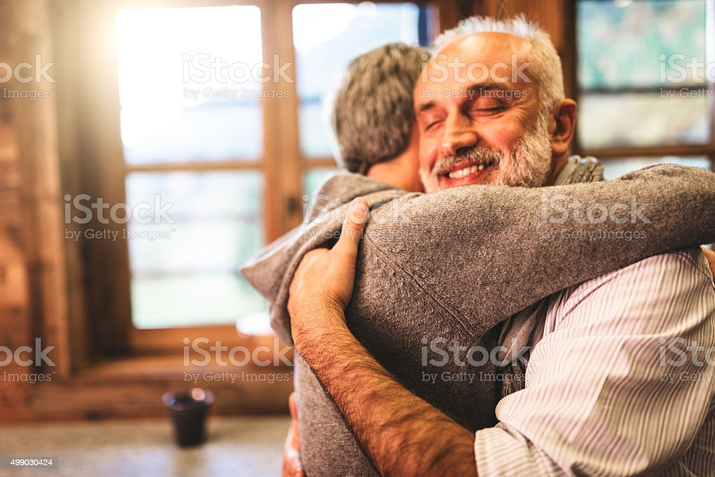 senior couple embracing passionate in the house - support concept stock photo