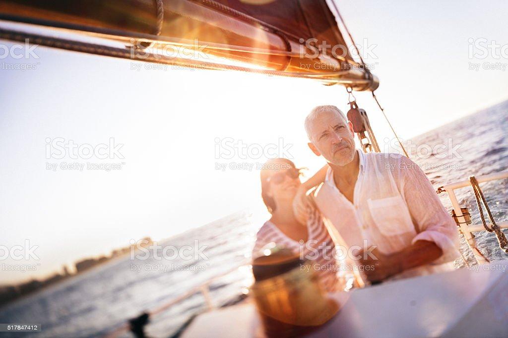 Senior couple enjoying a yacht cruise together stock photo