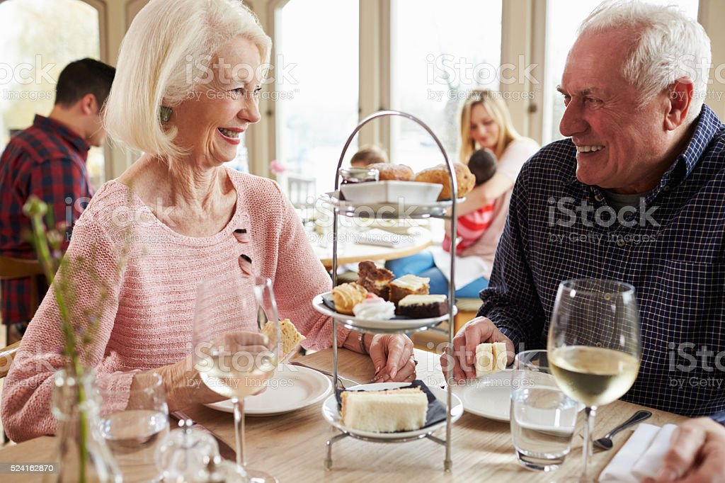 Senior Couple Enjoying Afternoon Tea In Restaurant Together stock photo