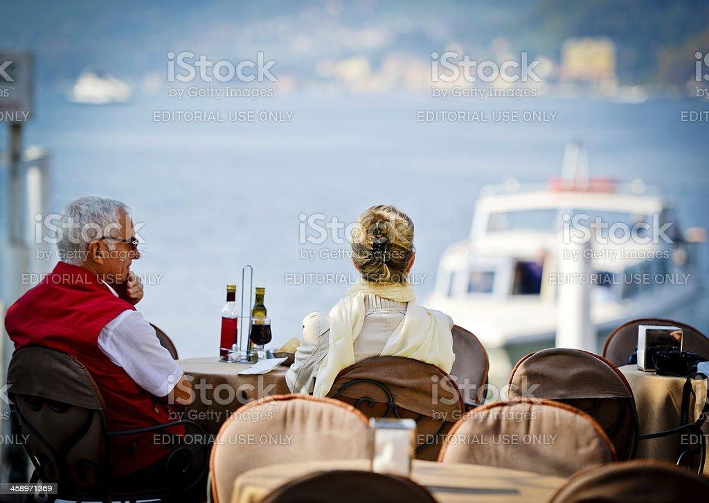 Senior couple enjoying Lake Como view in a restaurant royalty-free stock photo