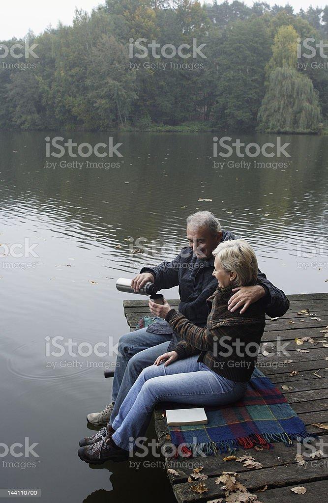 Senior couple enjoying morning coffee on wooden pier royalty-free stock photo