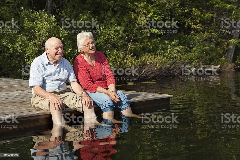 Senior couple enjoying retirement by a lake royalty-free stock photo