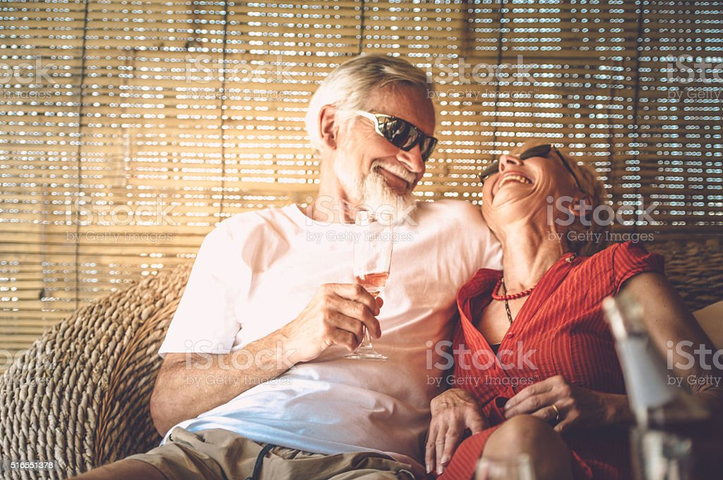 Senior couple enjoying summer vacations with champagne stock photo