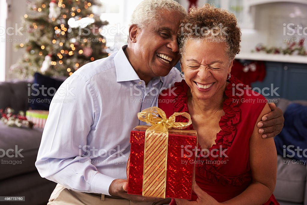 Senior Couple Exchanging Christmas Gifts At Home stock photo