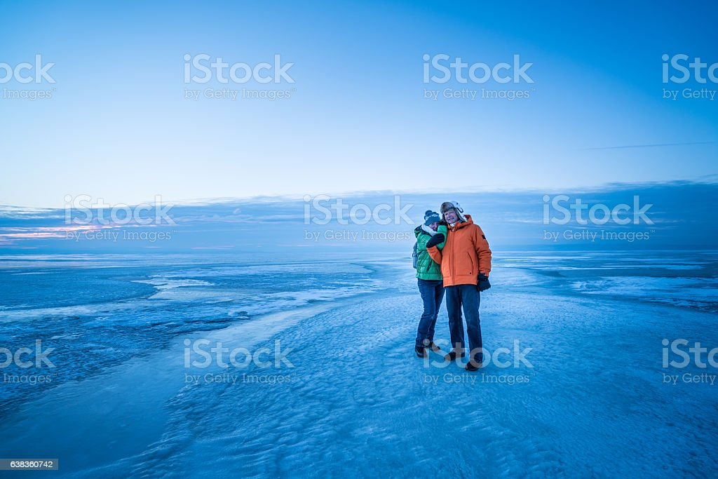 senior couple frozen lake hugging cold winters evening stock photo