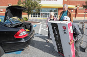 Senior couple gets help at store loading television into car
