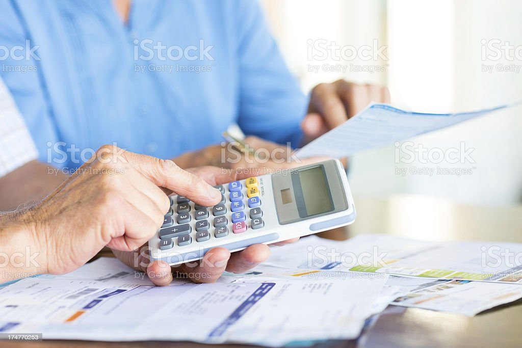 Senior Couple Going Through Paperwork And Calculating Bills. royalty-free stock photo