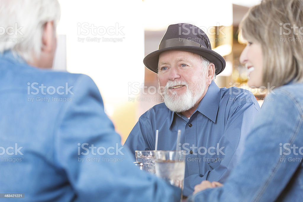 Senior couple having dinner with friends at local restaurant stock photo