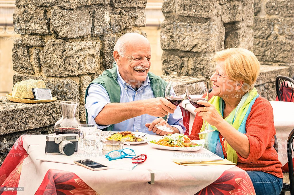 Senior couple having fun and eating at restaurant during travel stock photo