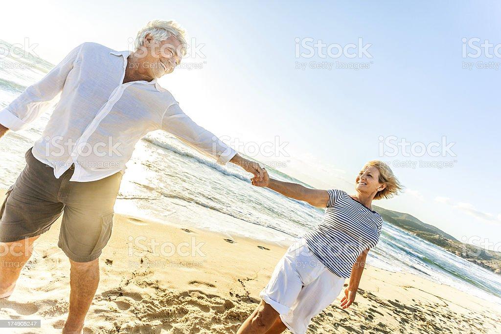 Senior couple having fun at a beach royalty-free stock photo