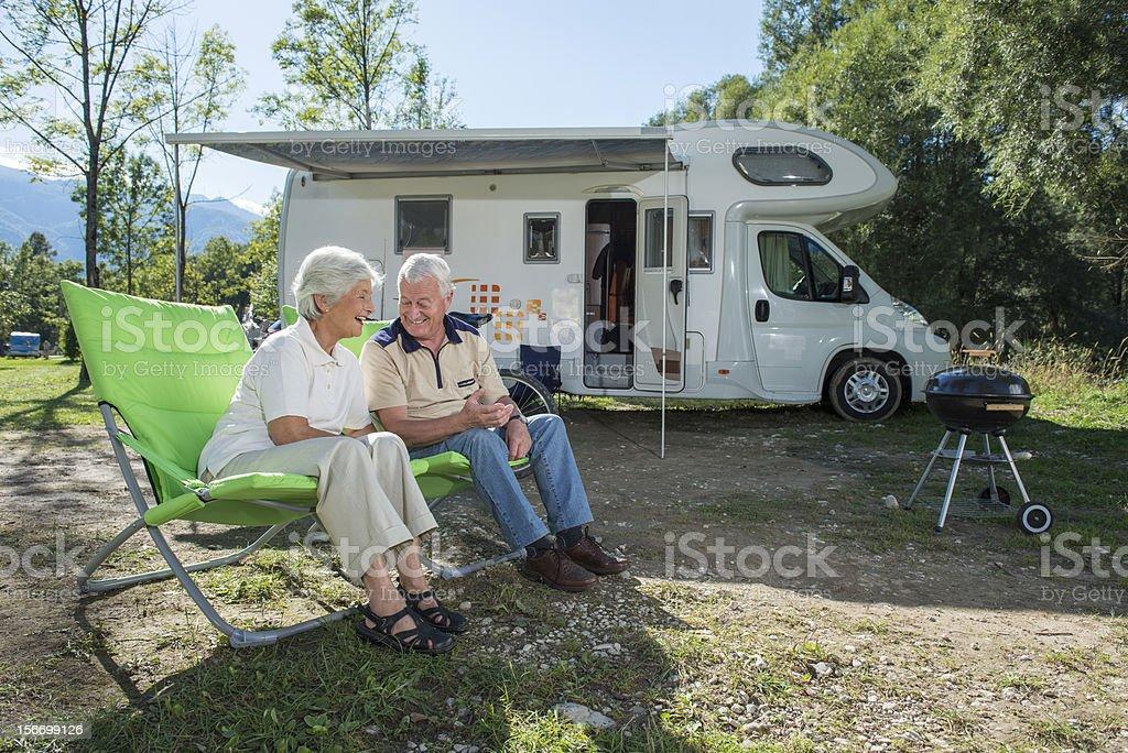 Senior couple having fun camping with camper van royalty-free stock photo