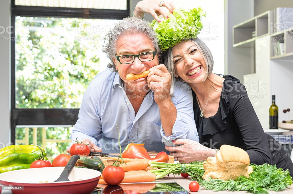 Senior couple having fun in kitchen cooking healthy food together stock photo