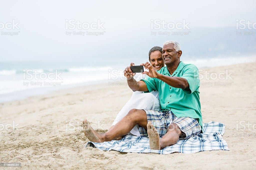 Senior couple having fun with smart phone on beach stock photo