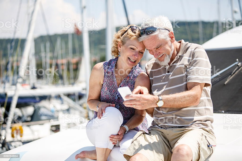 Senior couple having fun with smart phone on yacht stock photo