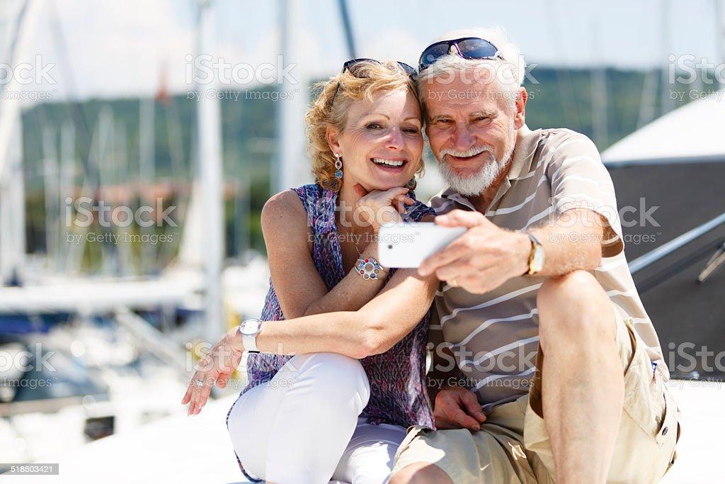 Senior couple having fun with smart phone on yacht stock photo