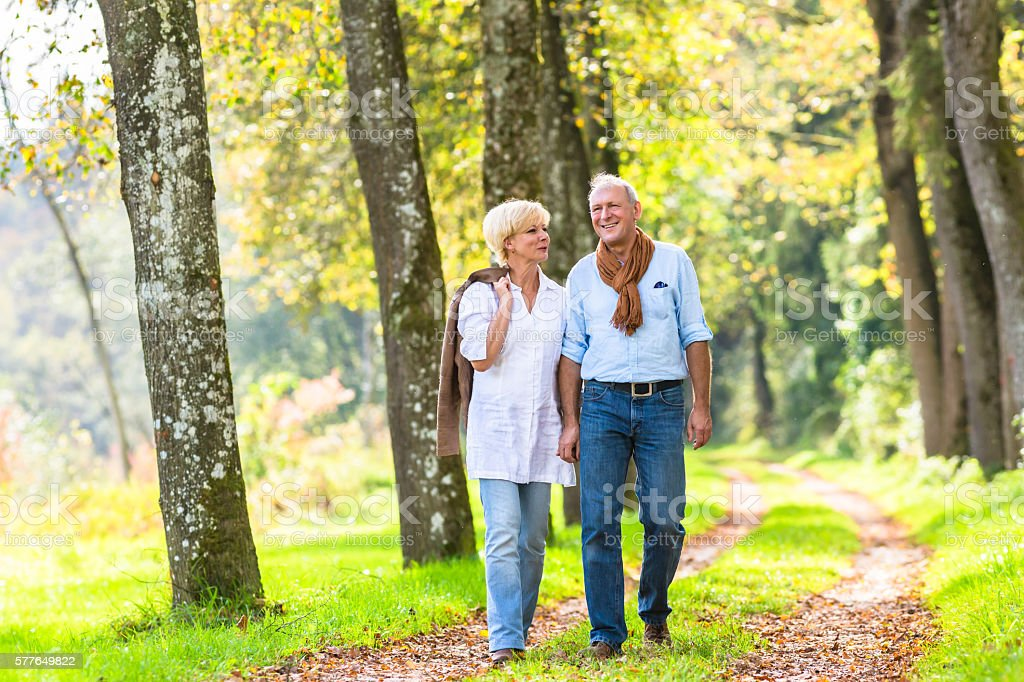 Senior couple having leisure walk in woods stock photo