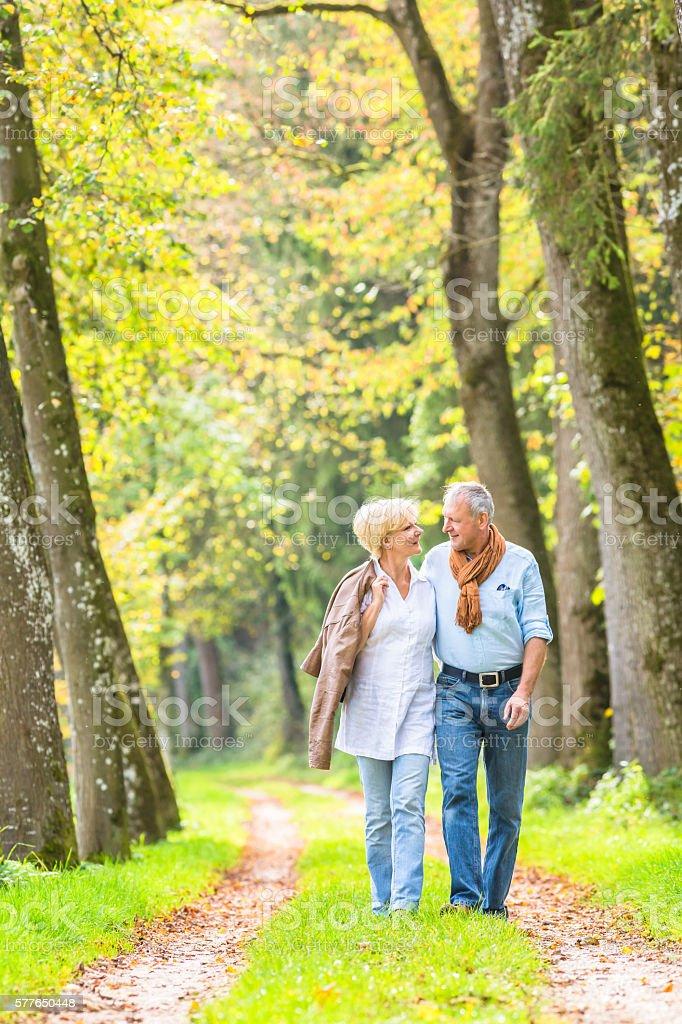 Senior couple having leisure walk in woods stock photo