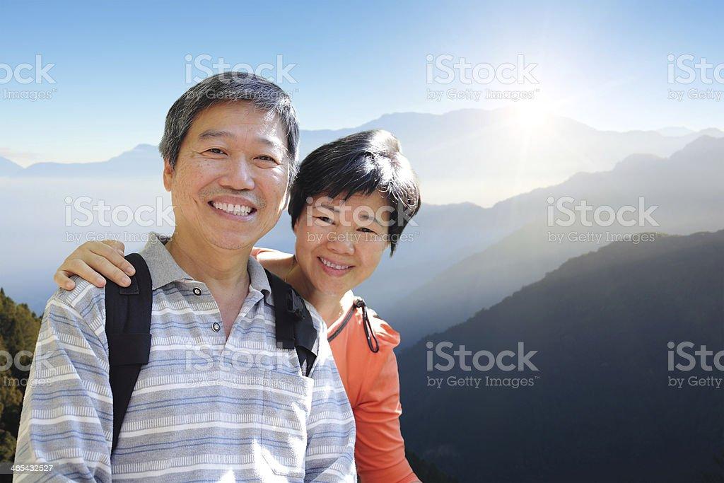 senior couple hiking with mountain stock photo