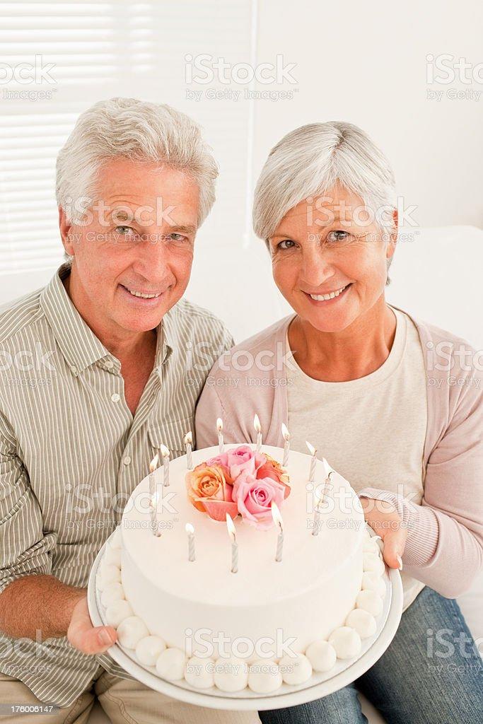 Senior couple holding anniversary cake royalty-free stock photo